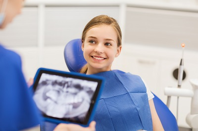smiling girl sitting at dental chair awaiting treatment