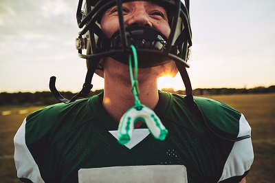 Closeup of a young American football player with his mouthguard hanging from his helmet during a team practice session