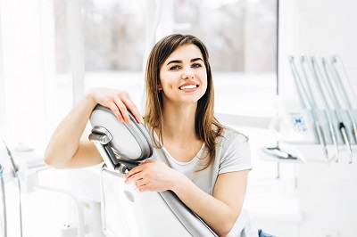 happy and smiling patient sitting in the dental chair