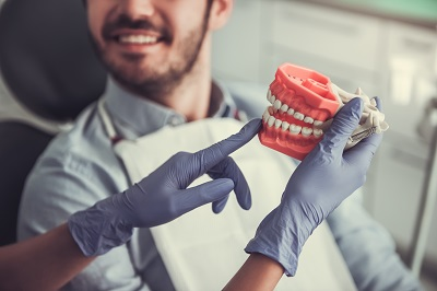 Cropped image of dentist holding a fake jaw, handsome young patient is smiling while sitting in chair at the dentist