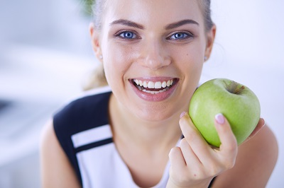 Close up portrait of healthy smiling woman with green apple