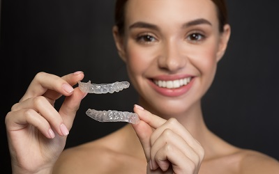 Close up of clear aligners in hands of happy girl who is standing and showing orthodontic device to the camera.