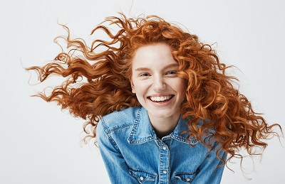 smiling redhead girl over white background