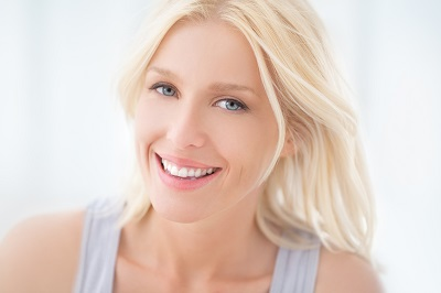 A portrait of a beautiful blonde woman smiling.