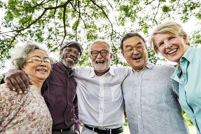 group of senior friends smiling at the park
