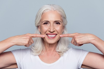 healthy senior woman pointing at her smile
