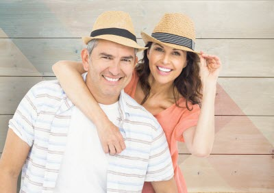 image of happy couple with hats against wood background