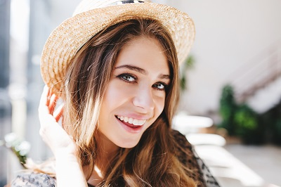portrait of excited girl wearing a straw hat with beautiful white smile