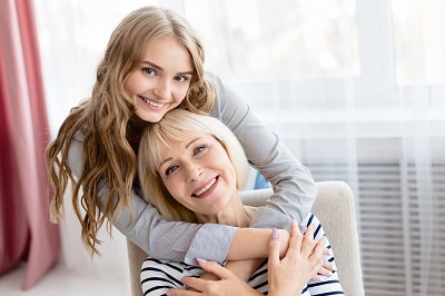 Young daughter cuddling her senior mother while smiling
