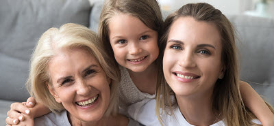 granddaughter, mother, and grandmother sitting together on sofa at home smiling