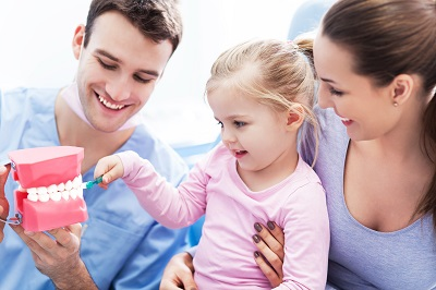 dental professional teaching little girl how to brush teeth