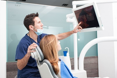 dental professional explaining treatment plan to patient while pointing to monitor