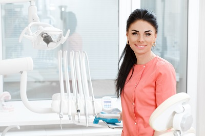Young beautiful female dental assistant smiling to the camera posing at the dental clinic