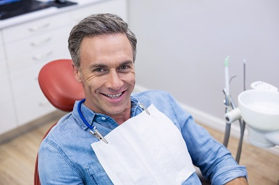 Smiling male patient sitting on dentist chair at clinic
