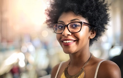 african american woman with glasses smiling in city background