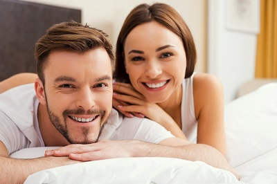 young couple relaxing on top of bed