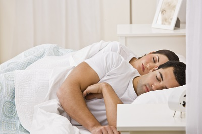 An attractive young couple sleeping.