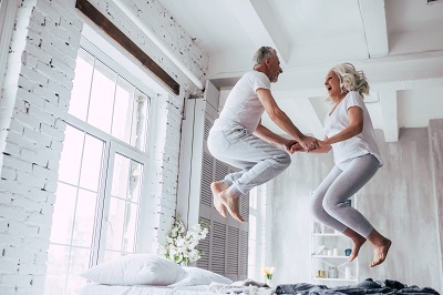 senior couple at home jumping on bed while holding hands and laughing