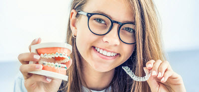 young girl holding invisalign clear braces and tooth model with metal braces
