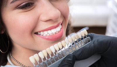 woman in dental office matching teeth color for veneer treatment