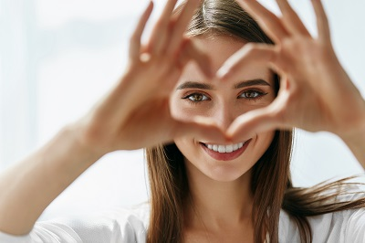 smiling woman making a heart shape with hands