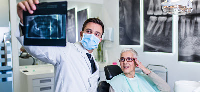 senior woman looking at dental x-ray in dental office