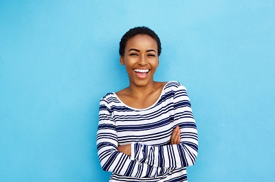 Portrait of happy young black woman laughing against blue wall