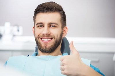 Portrait of happy patient in dental chair giving a thumbs up