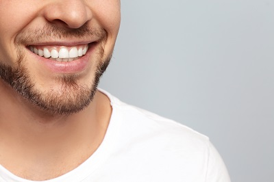 close up of young man's white smile over grey background