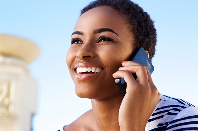 Close up portrait of smiling young african woman talking on mobile phone outside