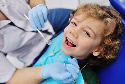 smiling child sitting in a blue chair dental