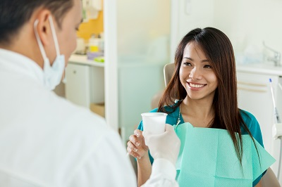 Smiling asian woman is taking a glass of water from dental professional