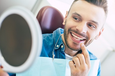 man looking at his new smile using mirror in dental office