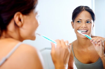 woman brushing teeth in home bathroom