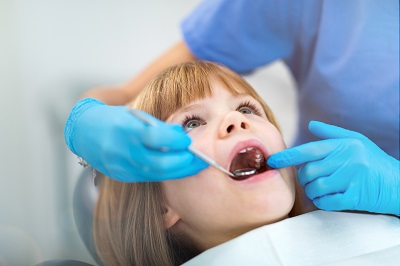 little girl getting a dental inspection