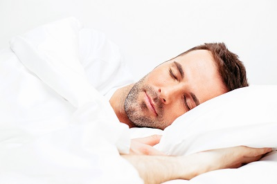 adult man sleeping in bed