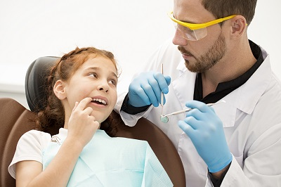 Pretty little girl visiting dentist at the clinic pointing at aching tooth in her mouth