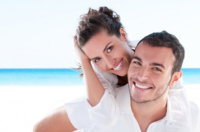 young couple at the beach smiling