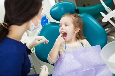 little girl pointing at her molar tooth in dental office