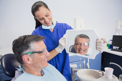 senior man looking at mirror checking out his smile in dental office