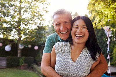 Portrait Of Loving Mature Couple In Back Yard Garden
