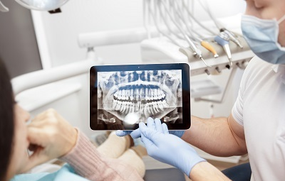 patient looking at dental x-ray on tablet
