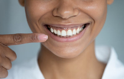 woman pointing at smile with healthy gums