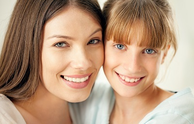Close-up of a mother and her cute daughter smiling and posing
