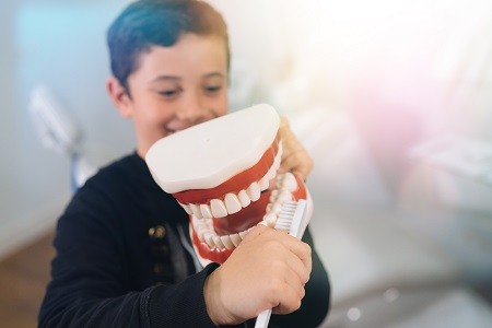 little boy learning how to brush using tooth model in dental office