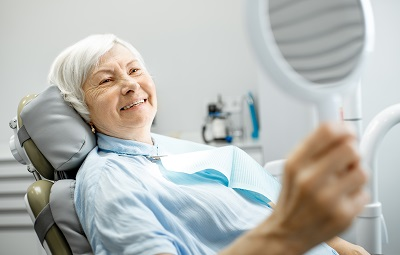 senior woman checking out her smile in dental office
