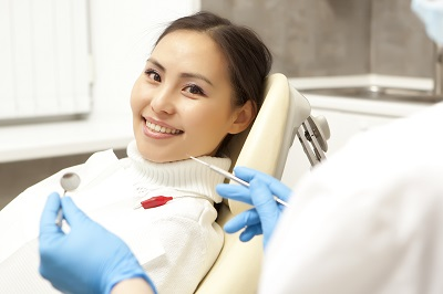 smiling woman sitting in dental chair awaiting treatment