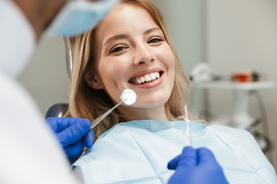 young woman sitting in dental chair getting a dental inspection