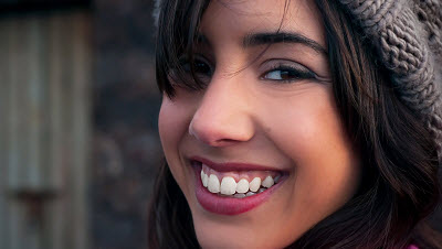 close up of young woman's face with a big smile