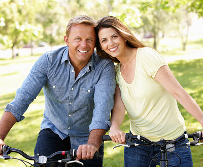 smiling couple riding bycicles together